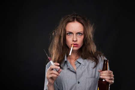 chica fumando: retrato de mujer de fumar cigarrillos colgando de su boca. mujer sosteniendo la jeringa y la botella sobre fondo negro