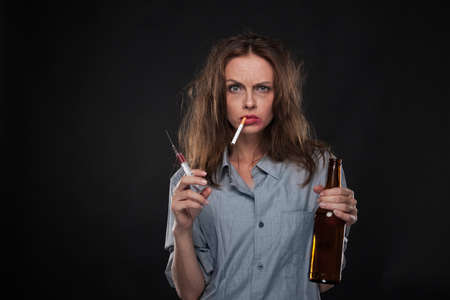waist up: portrait of woman smoking cigarette hanging out of her mouth. waist up of woman holding syringe and bottle on black background
