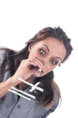 girl sniffing cocaine on white background. Young woman snorting cocaine with bill close-up  Stock Photo