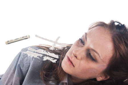 Young woman and cross made of cocaine. Drug addicted woman lying on table and lines of cocaine. Stock Photo