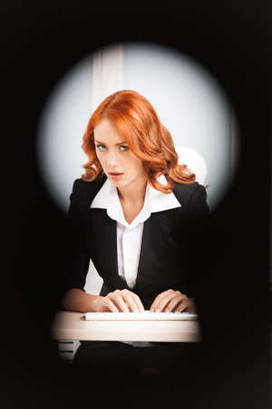 spy girl: keyhole view of young pretty business woman. red-hair girl work on notebook computer in bright modern office indoors Stock Photo