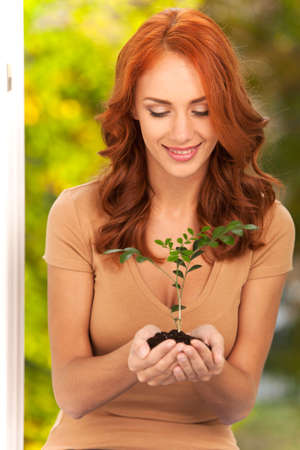 redhaired: Woman holding little plant in her hands. Womans hands holding soil with plant and smiling