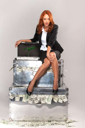 upstairs: business woman sitting on suitcase full of money. Woman sitting on suitcase with cash and plant on white background