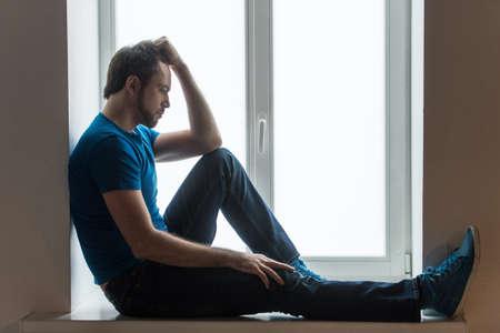 hombre solo: Apuesto joven sentado en el alféizar de la ventana. Individuo que sostiene la cabeza y vestido con camisa azul y pantalones vaqueros