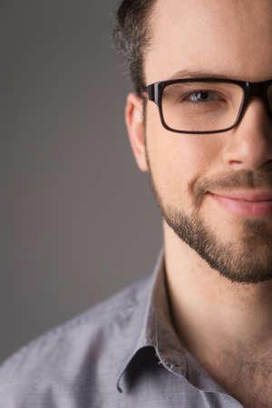 Portret van een jonge casual man met een bril lachend. Jonge knappe man half gezicht op grijs Stockfoto