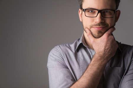 あごを保持している魅力的な若い男のクローズ アップの肖像画。メガネと灰色の背景に立っている人