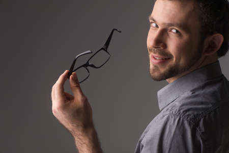 back view portrait of attractive young man holding chin. Man standing on gray background holding glasses photo