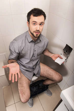 pantalones abajo: Primer plano del hombre en el papel higiénico holding. Hombre adulto sentado en cuarto de baño o aseo wc Foto de archivo