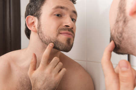 Closeup of young man examining his stubble in mirror. Man looks at his beard and thought about shaving