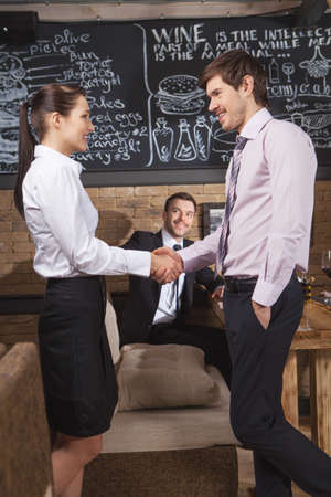 Young attractive businessman and businesswoman at cafe. business people shake hands each other at meeting  photo