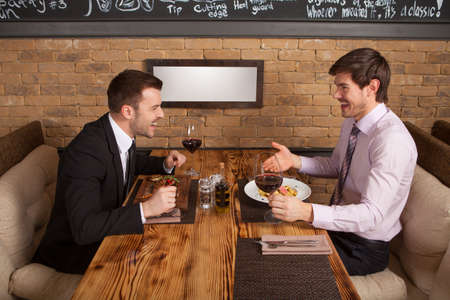 twee vrienden zitten in een cafe en het eten van de lunch. twee collega's ontmoetten elkaar in het restaurant om zaken te bespreken