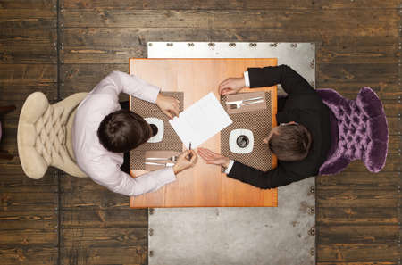 two people talking: two friends sitting in cafe and eating lunch. top view of two colleagues met in restaurant