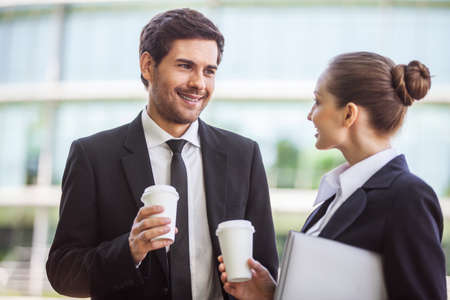 Young businesswoman with male colleague discussing. businessman and businesswomen drinking coffee outside Foto de archivo