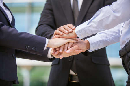 Closeup of business team holding hands together. close-up of three hands on top of each other  Stock Photo