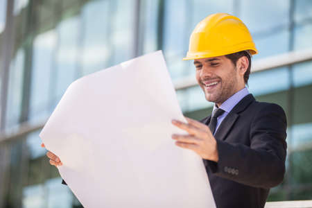 reviewer: Architect in yellow hardhat holding plan. young construction reviewer wearing workwear