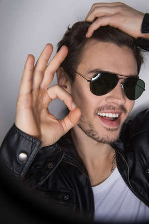 hot guy: Male model Head shot with sunglasses. handsome guy standing on white background and showing ok sign Stock Photo