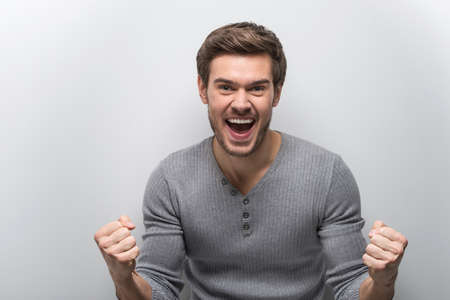 standing against: Portrait Of Smiling Man With Fists Up. happy guy standing against white background
