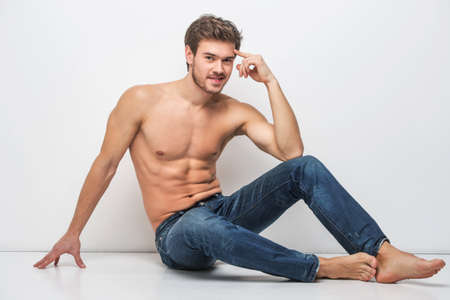 niño sin camisa: Chico guapo en pantalones vaqueros con el torso desnudo. hombre sentado en el suelo cerca de la pared