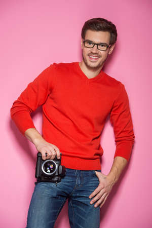 Portrait of young male with professional digital camera. man in glasses and jeans standing over pink background.  photo