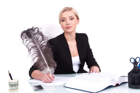 looking into camera: Young businesswoman looking into camera on white background. beautiful young woman writing at table using feather