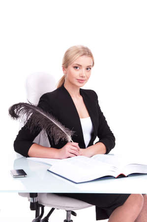 undersign: Young businesswoman working on white background and looking into camera. beautiful young woman writing at table using feather