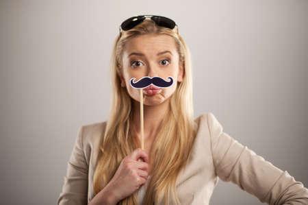 bigote: Mujer joven atractiva que sostiene el bigote en palo. ni�a bonita de pie sobre fondo gris con gafas de sol y bigotes