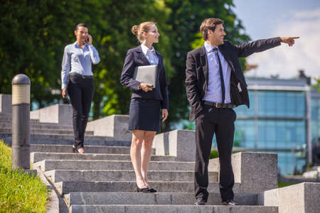 sidewalk talk: three business people standing on stairway. man wearing suit pointing and smiling