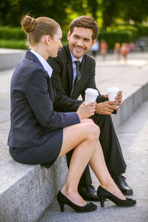 personas tomando cafe: La gente de negocios el consumo de caf� fuera. Socios comerciales que discuten mientras que en las escaleras