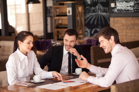 Three friends discuss graph lying on table at cafe. Business people having meeting at coffee table, smiling.