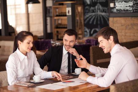 Drie vrienden bespreken grafiek liggen op tafel in cafe. Mensen uit het bedrijfsleven die vergadering op koffietafel, glimlachend.