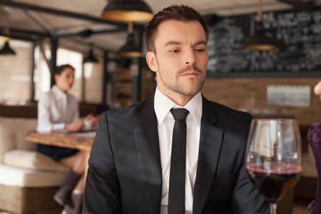 Stylish young man sitting in bar. Handsome man drinking glass of red wine in bar  photo
