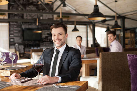 elegant business man: Stylish young man sitting in restaurant. Handsome man drinking glass of red wine in cafe