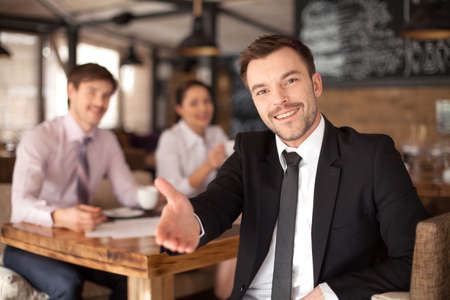 Stylish young man sitting in restaurant. closeup of smiling man giving hand and colleagues on background photo