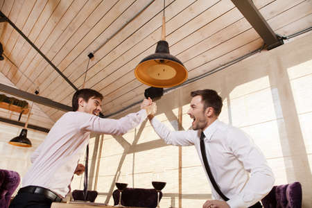 feeling happy: men laugh together while meeting in cafe. two man holding hands and greeting each other inside