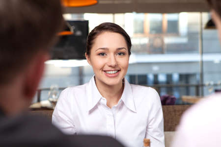 looking into camera: Young woman looking into camera and smiling. pretty girl eating healthy salad lunch in cafe with friends