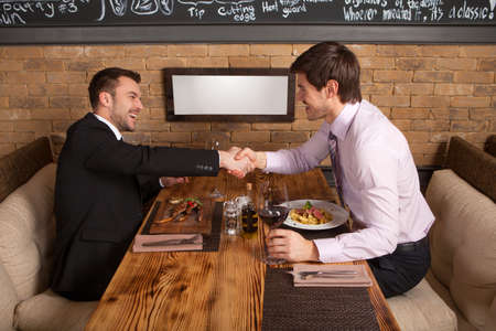 men laugh together while sitting in cafe. two man holding hands and greeting each other at table