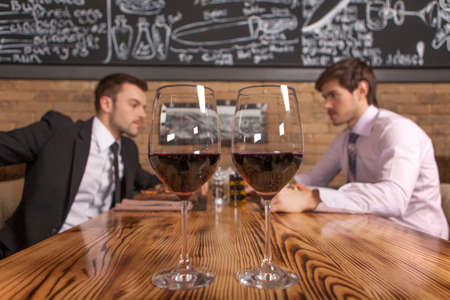 two friends sitting in cafe and eating lunch. two glasses of wine standing on foreground in restaurant photo