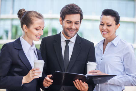 personas tomando cafe: Sonrientes mujeres de negocios jovenes y hombre de negocios. tres personas bebiendo caf� fuera