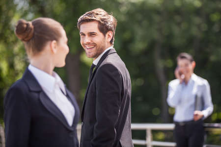 Three happy business partner people talking outside. brunette girl looking at man and smiling outside photo