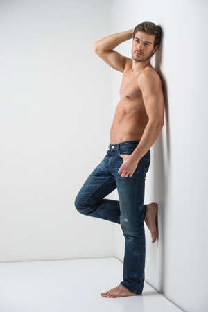lean: Healthy muscular young man in jeans. Isolated on white background guy leaning on wall