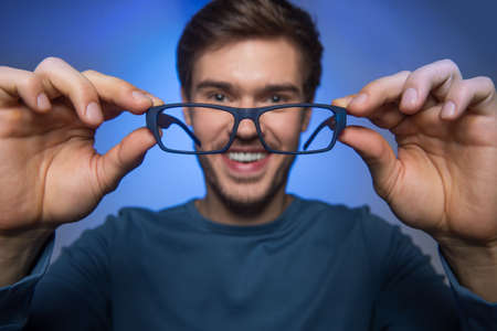 man wearing glasses to improve vision. handsome guy holding glasses on blue background. photo