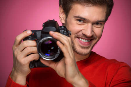 looking into camera: Portrait of young male with professional digital camera. man looking into camera over red background.  Stock Photo