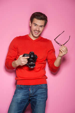 Portrait of young male with professional digital camera. man removed glasses standing over pink background.  photo