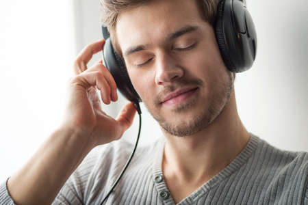 Handsome young man listening to music. guy wearing headphones with closed eyes on grey background Foto de archivo