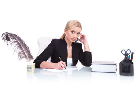 writing book: Portrait of serious business woman sitting on her desk. beautiful young woman writing at table and talking on cell phone
