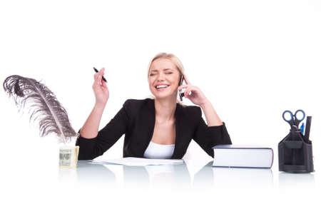 Portrait of happy business woman sitting on her desk. beautiful young woman laughing at table and talking on cell phone photo