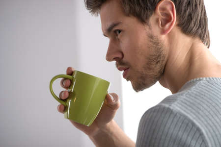 hot guy: closeup portrait of thoughtful man having coffee. Handsome young man holding mug