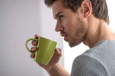 cute guy: closeup portrait of thoughtful man having coffee. Handsome young man holding mug