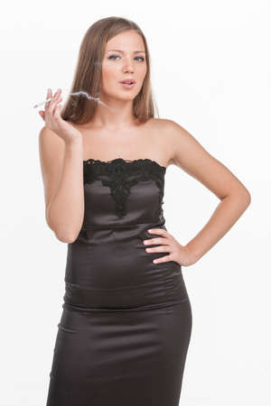 chica fumando: joven hermosa chica cigarrillo fumar. Morena exhalando humo de cigarrillo en el fondo blanco