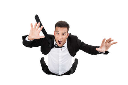 Scared young businessman in falling position. flying businessman on white background and crying